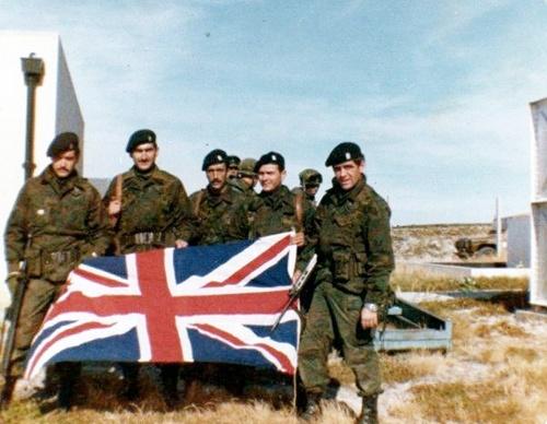 49 Cap.(pm) Luis Castagnari, junto a Suboficiales del GOE, al arriar la bandera inglesa el 2 de abril de 1982, en Pto. Argentino
